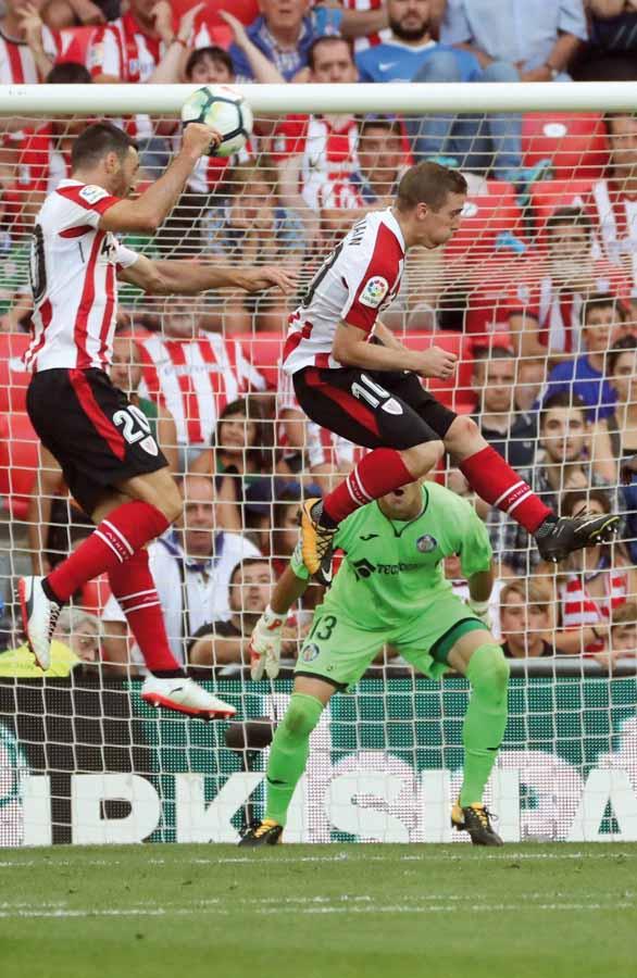 GRA338. BILBAO, 21/01/2016.- Los jugadores del Athletic de Bilbao Aritz Aduriz (i) e Iker Muniain (d) intentan cabecear el balón aéreo ante el portero del Getafe F.C. Vicente Guaita (fondo), durante el partido correspondiente a la primera jornada de LaLiga Santander que se disputa esta tarde en el estadio de San Mamés. EFE/Luis Tejido